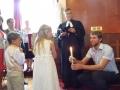 Didzis Mucenieks pasniedz sveci Luīzei. Svece simbolizē Kristus gaismu. Jēzus teica: Es esmu pasaules gaisma; kas seko man, tas patiesi nestaigās tumsībā, bet tam būs dzīvības gaisma.