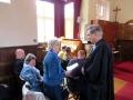 Prāvests pasniedz Archibīskapa Atzinības rakstu Ainai Rumbai