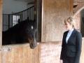 Mācītāja Elīza Zikmane pie zirga staļļa. Latvieši pārbūvēja staļļus istabās, kur dzīvoja vecie ļaudies. Tagadējie īpašnieki tos pārvērtuši atkal staļļos